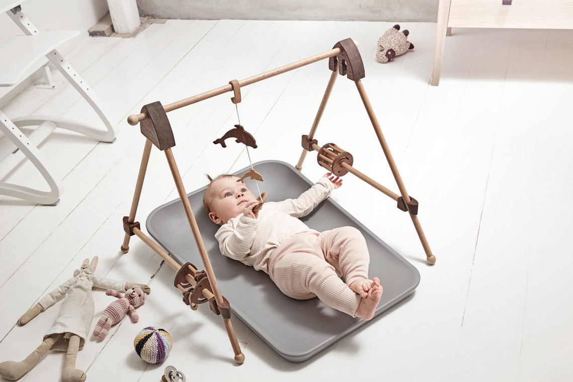 Baby laying on a grey matty changer strapped in playing with a wooden toy