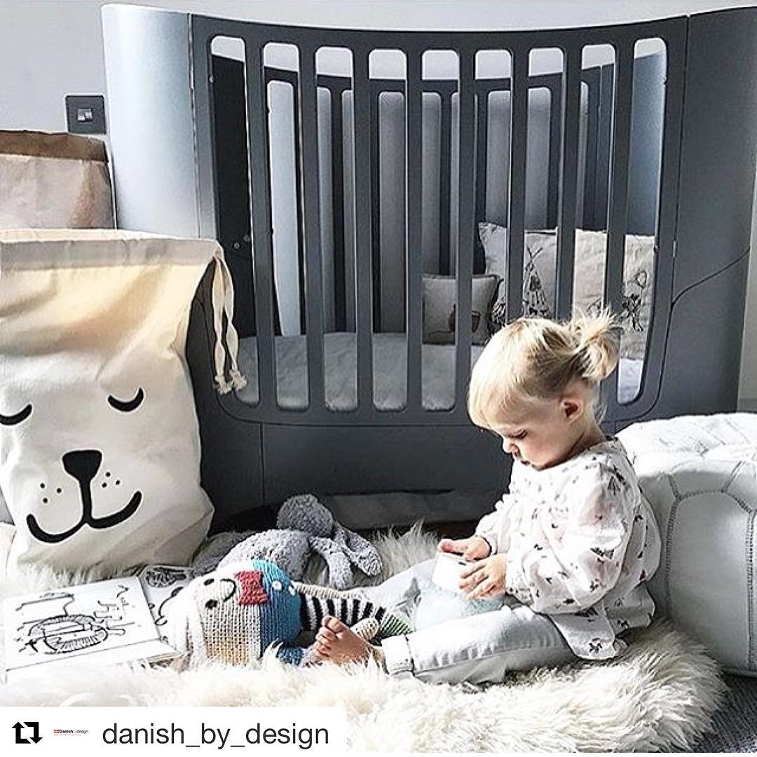 Baby nursery with dark grey oval leander crib, little girl sitting on a fluffy white rug on the floor leaning on ottoman