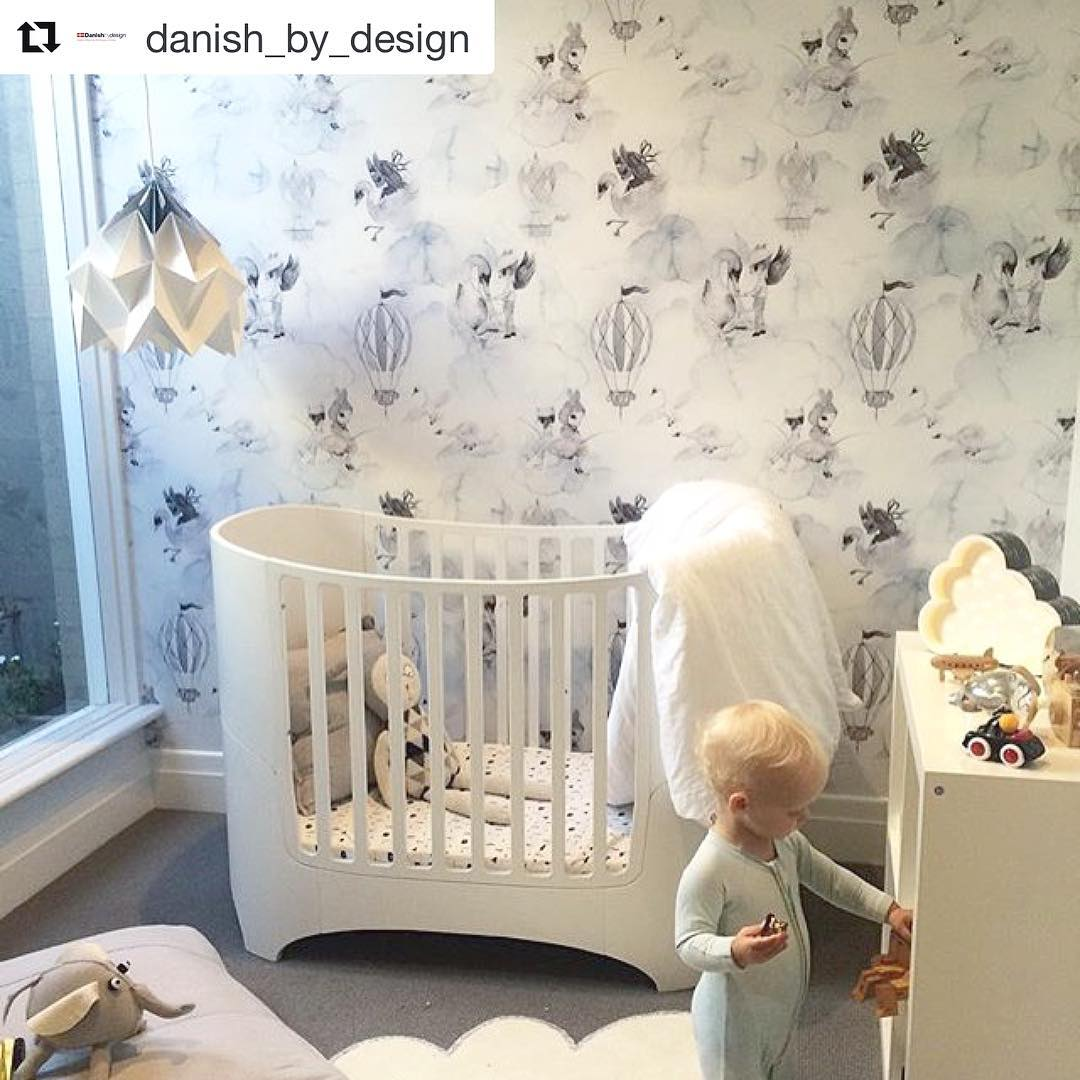 Baby nursery with grey and white wallpaper with hot air balloons, a white sleek oval crib, baby putting toy away on dresser