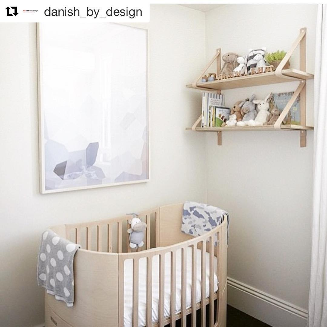 baby nursery with big framed picture on wall, two shelves with books and little stuffed animals, a beige wooden sleek oval crib