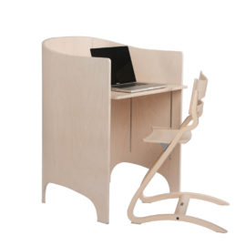 Wooden changing table transformed into a desk with a chair and an open laptop