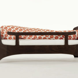 junior bed with optional safety gate in a dark brown wood and orange and white sheets