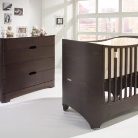baby nursery featuring a sleek oval wooden crib in a dark brown cocoa color and a 4 drawer dresser