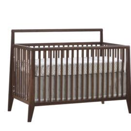dark brown wood convertible crib with white glossy facade and a mattress with grey polka dots