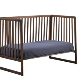 rio dark brown wooden classic crib converted into a daybed with navy sheets