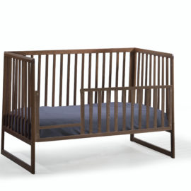 rio dark brown wooden classic crib converted into a toddler bed with toddler gates with navy sheets