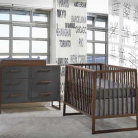 baby nursery with names of cities and tic tac toe on walls, dark walnut wood crib with grey sheets, double dresser with glossy grey facades and wooden changing tray