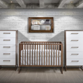 Baby room with a white brick wall, a dark brown wood crib, 2 dressers with a white drawer facade