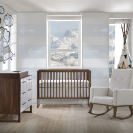Grey and blue baby nursery with rio walnut crib, double dresser with changing tray on top and a rocking chair with white linen cushions