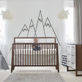 White bedroom with wooden crib with a baby sitting and laughing in it and double dresser in walnut & glossy white with a black and white teepee and mountain wallpaper