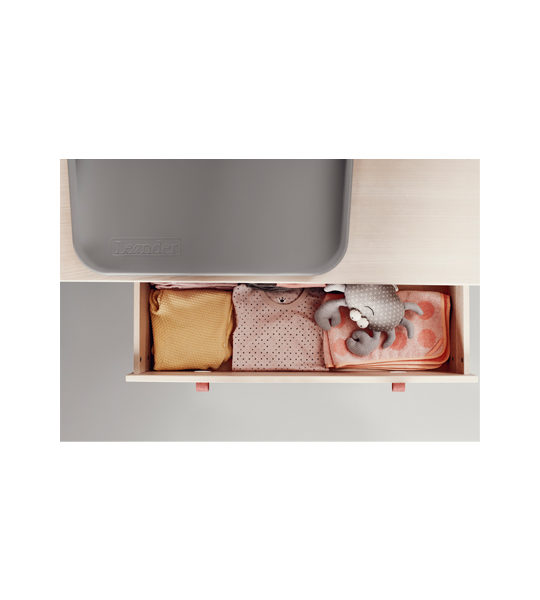 Picture from above of Linea wooden dresser with an open drawer showing folded pink and yellow baby girl clothes and grey matty changer
