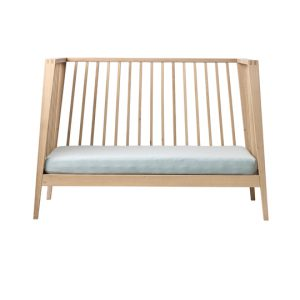Linea wooden crib opened to turn into a daybed with misty blue mattress sheets