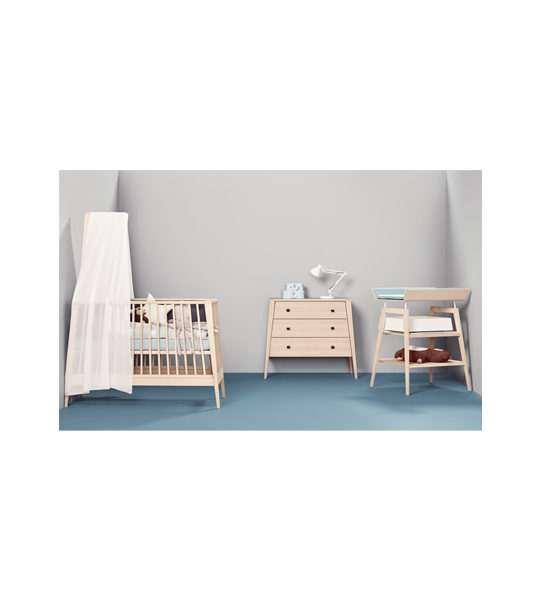 Grey nursery with blue floors with wooden linea crib, 3 drawer dresser and changing table with blue mat and blue sheets