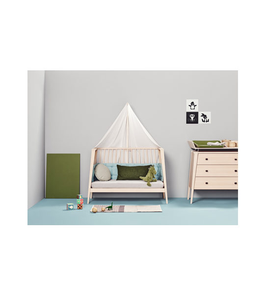 Grey nursery with blue floors with wooden linea crib open and turned into a daybed with grey sheets and green pillow and dinosaur toy, 3 drawer dresser and green changing table