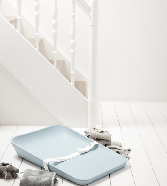 Matty Changer Soft blue with white strap on white wooden floor and grey folded towels