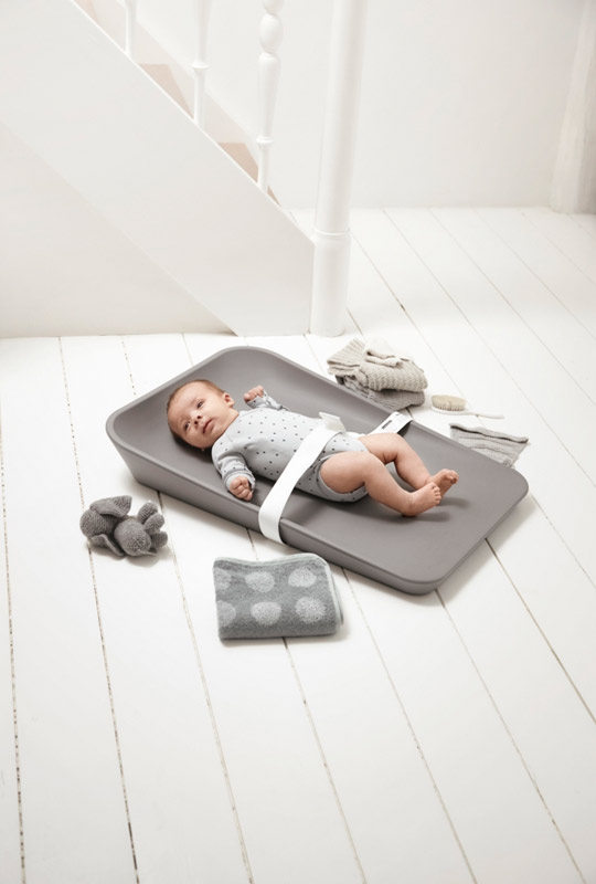Matty Changer in grey with a baby strapped in with a white strap on a white wooden floor with grey folded towels