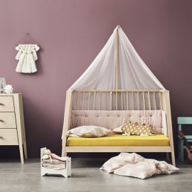 Purple baby room with linea 3 drawer dresser, crib turned into a junior bed with yellow sheets and pink mats