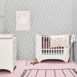 Grey baby nursery with grey and white polka dot wallpaper, white leander oval crib and dresser with pink floors