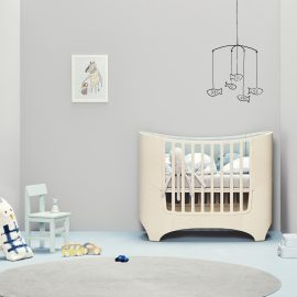 Light grey baby nursery with blue floors, leander oval crib with grey sheets and blue mats, grey area rug