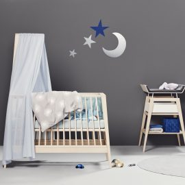 Grey Baby room with stars and moon decal on wall, linea crib with blue sheets and linea changing table with a black mat