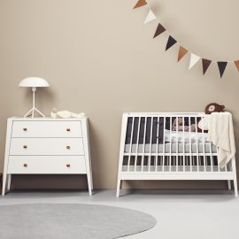 Beige baby room with white linea 3 drawer dresser and crib with grey sheets