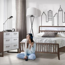 White teen bedroom with walnut wood double bed and double dresser with white glossy finished, city outline wallpaper and sheets with a teen sitting on floor listening to music