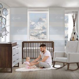 Grey and blue baby nursery with rio walnut crib, double dresser and changing tray with baby and dad sitting on floor playing.