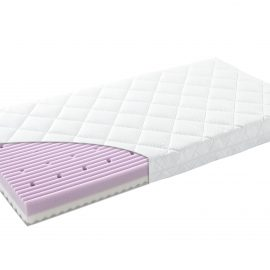 Close up of a crib mattress with exposed corner revealing foam interior