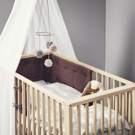 Linea crib in a grey bedroom with white curtains, pink and grey mobile