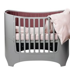 Leander grey convertible oval crib with pink sheets