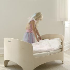Leander convertible crib turned into a junior bed with little blond girl making her bed