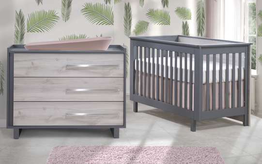 Nursery with green leaf wall decals with charcoal crib and 3 drawer dresser with white wood facades